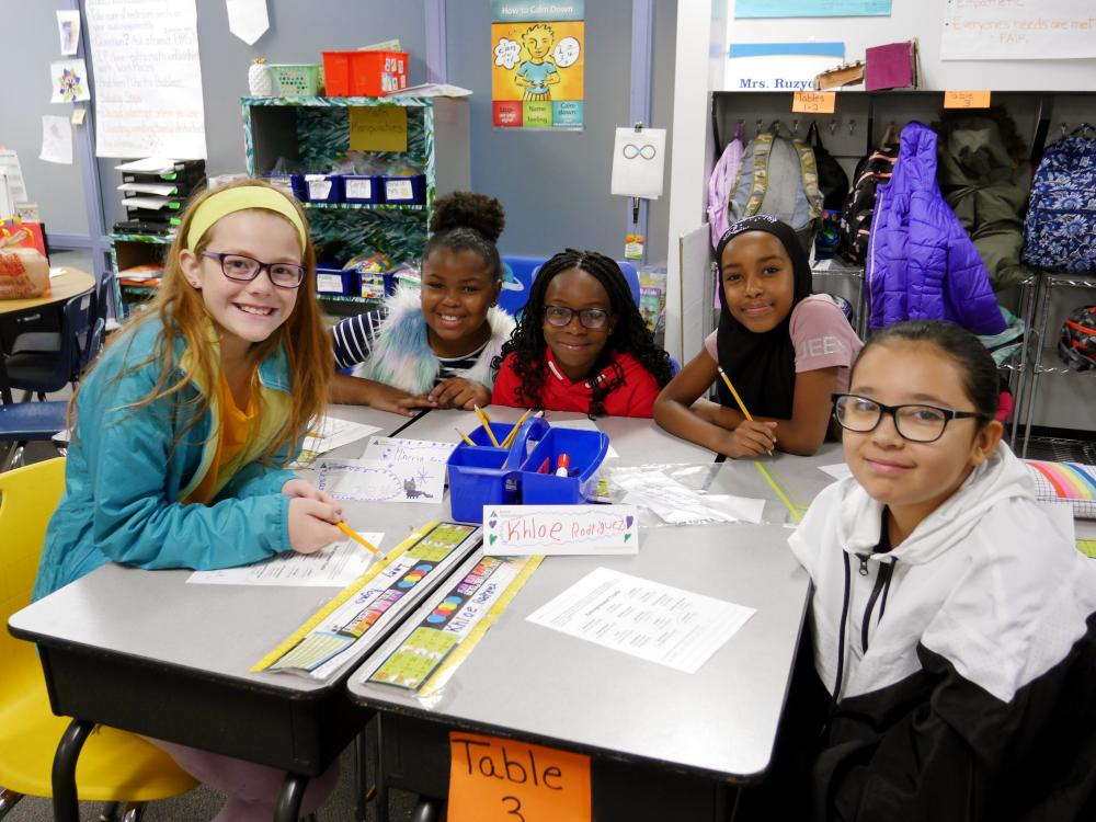 Small group of fourth grade student working on a JA activity